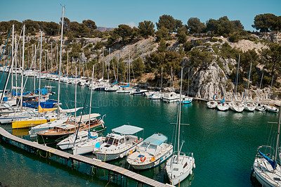 Buy stock photo Shot of yachts and sail boats lined up alongside each other in a harbor in Spain