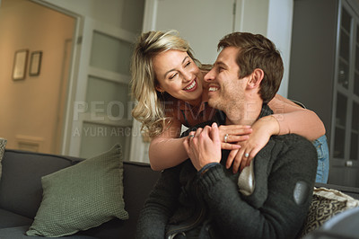 Buy stock photo Shot of a happy young couple relaxing on the sofa at home