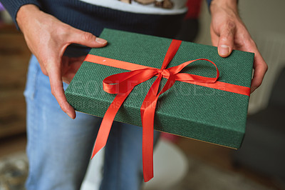 Buy stock photo Cropped shot of a man holding a Christmas gift at home
