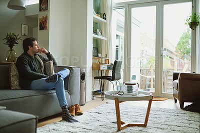 Buy stock photo Shot of a young man sitting on the sofa and looking thoughtfully out of a window at home