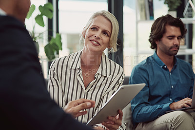 Buy stock photo Shot of a mature businesswoman using a digital tablet while working with a colleague in an office