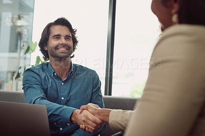 Buy stock photo Shot of a young businessman shaking hands with a colleague in an office