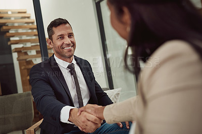 Buy stock photo Shot of a mature businessman shaking hands with a colleague in an office
