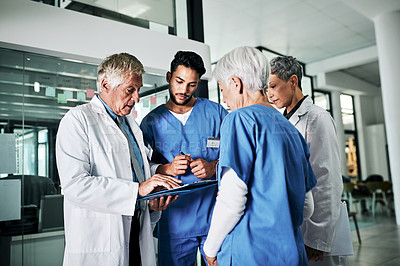 Buy stock photo Cropped shot of a diverse group of medical practitioners discussing a file while standing in a hospital