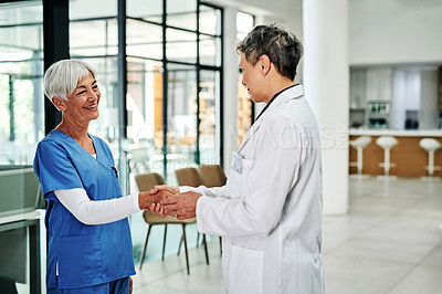Buy stock photo Cropped shot of an attractive mature female nurse shaking hands with a female doctor in a hospital