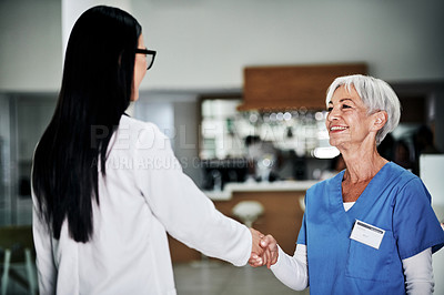 Buy stock photo Cropped shot of an attractive mature female nurse shaking hands with a young female doctor in a hospital