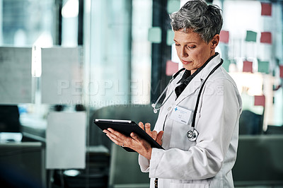 Buy stock photo Cropped shot of an attractive mature female doctor using a digital tablet while standing in a hospital