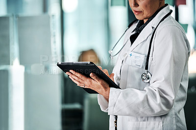 Buy stock photo Cropped shot of an unrecognizable female doctor using a digital tablet while standing in a hospital