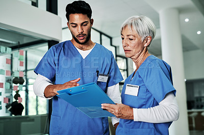 Buy stock photo Cropped shot of two medical practitioners discussing a file while standing in a hospital
