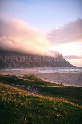 Buy stock photo Cropped shot of a mountainside beach at sunset