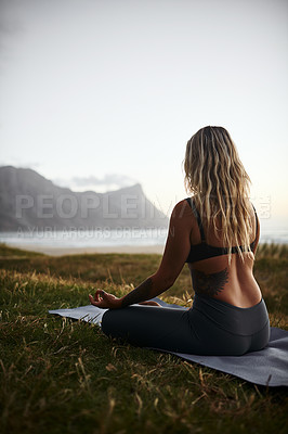 Buy stock photo Full length shot of an unrecognizable woman sitting alone and meditating during a relaxing day outdoors