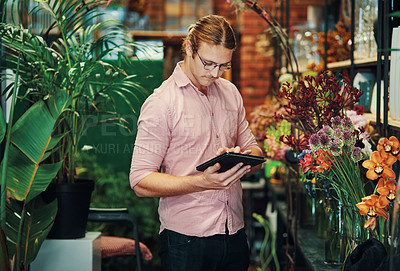 Buy stock photo Cropped shot of a handsome young businessman standing alone in his flower shop and using a tablet