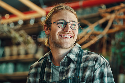Buy stock photo Cropped shot of a handsome young businessman standing alone in his flower shop during the day