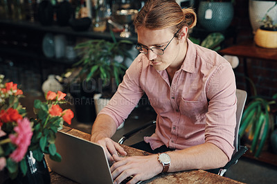 Buy stock photo Cropped shot of a handsome young businessman sitting alone in his floristry and using his laptop