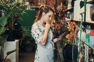 Buy stock photo Cropped shot of an attractive young businesswoman standing alone in her floristry and looking contemplative while using a tablet