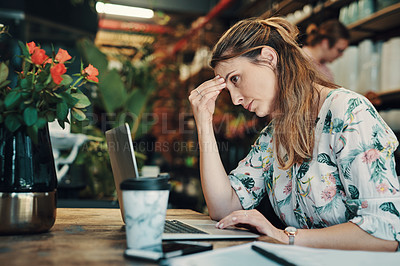 Buy stock photo Cropped shot of an attractive young businesswoman sitting alone in her floristry and feeling stressed while using her laptop