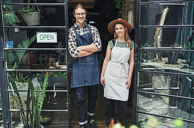 Buy stock photo Cropped portrait of two young business owners standing at the entrance of their floristry together