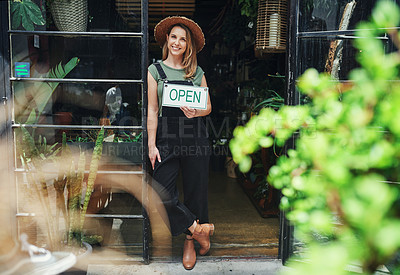 Buy stock photo Full length portrait of an attractive young business owner standing alone and holding the open sign at the floristry entrance