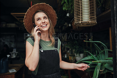 Buy stock photo Cropped shot of an attractive young business owner standing alone at the entrance of her floristry while on a phonecall