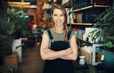 Buy stock photo Cropped portrait of an attractive young business owner standing in her floristry alone with her arms folded