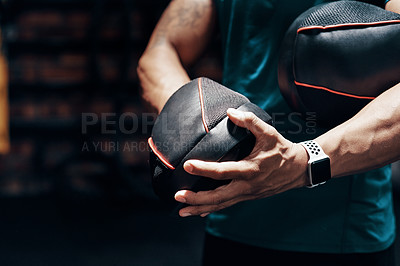 Buy stock photo Cropped shot of an an unrecognizable sportsman putting on protective gloves while working out in a gym