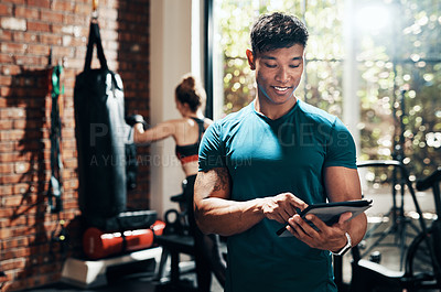 Buy stock photo Cropped shot of a handsome young sportsman using a digital tablet in a gym with his fitness partner in the background