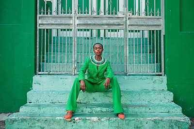 Buy stock photo Portrait of an attractive young woman seated on steps while wearing a green outfit outside during the day