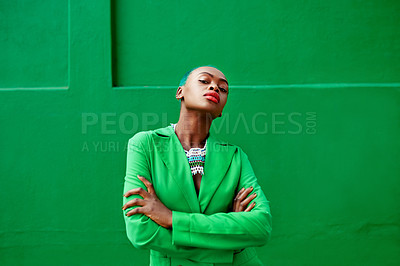 Buy stock photo Portrait of an attractive young woman posing while standing against a green background outside during the day