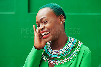 Buy stock photo Cropped shot of a cheerful young woman posing while standing against a green background outside during the day