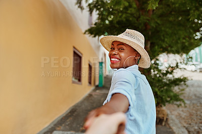 Buy stock photo Portrait of a cheerful young woman looking back and leading an unrecognizable person by the hand to walk with her outside during the day
