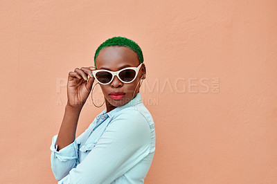 Buy stock photo Portrait of an attractive young woman posing while standing against a orange background outside during the day