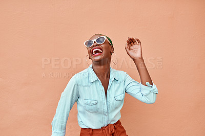 Buy stock photo Cropped shot of a cheerful young woman dancing against a orange background outside during the day
