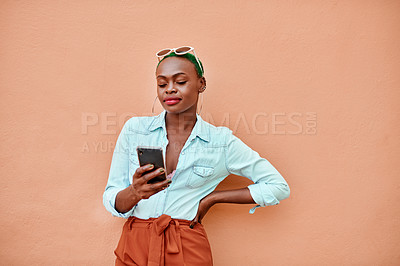 Buy stock photo Cropped shot of an attractive young woman texting on her cellphone while standing against a orange background