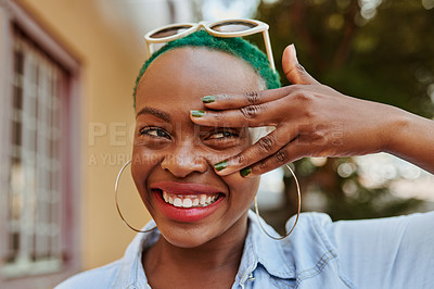 Buy stock photo Cropped shot of an attractive young woman peeking through her hand while standing outside during the day