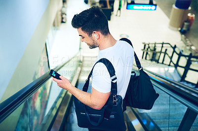 Buy stock photo Shot of a young man using a smartphone while going down an escalator in an airport window