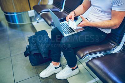 Buy stock photo Cropped shot of a man using a laptop and getting his passport ready before his flight at an airport