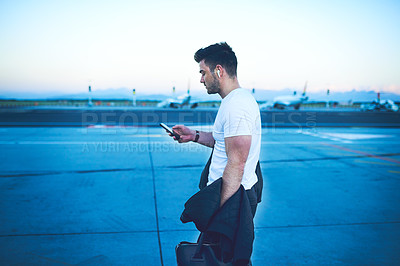 Buy stock photo Shot of a young man using a smartphone while boarding a flight at an airport