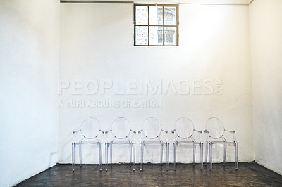Buy stock photo Shot of a row of empty chairs against a white wall