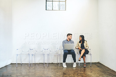 Buy stock photo Shot of two businesspeople having a discussion while sitting against a white wall in an office