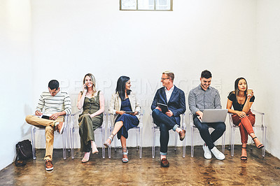 Buy stock photo Shot of a group of candidates using digital devices while waiting in line