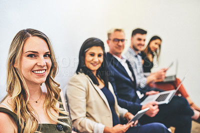 Buy stock photo Portrait of a young woman sitting in line with other candidates in the background
