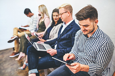 Buy stock photo Shot of a young man using a digital tablet while sitting in line with other candidates in the background