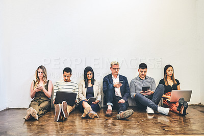 Buy stock photo Shot of a group of businesspeople using digital devices while sitting on the floor against a white wall