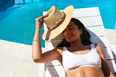 Buy stock photo Cropped shot of a beautiful young woman relaxing on a lounger by the poolside