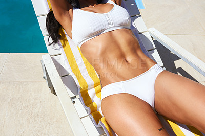 Buy stock photo Cropped shot of a fit young woman relaxing on a lounger