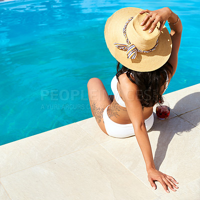 Buy stock photo Rearview shot of a young woman relaxing by the pool on a sunny day