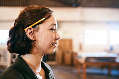 Buy stock photo Cropped of a female carpenter posing standing with a pencil behind her ear