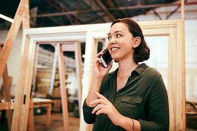 Buy stock photo Shot of a female carpenter talking on her cellphone while standing in her workshop