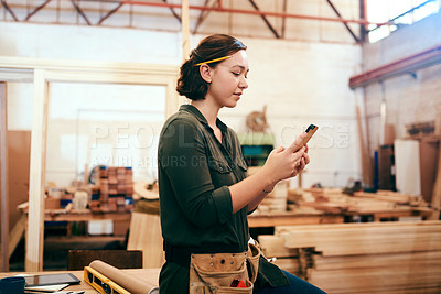 Buy stock photo Cropped shot of a female carpenter using her cellphone in her workshop