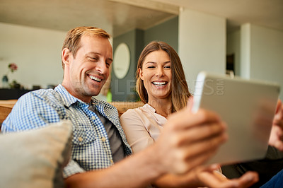 Buy stock photo Shot of a happy young couple using a digital tablet together while relaxing on the sofa at home